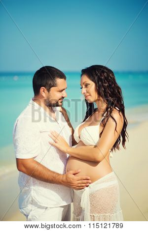 Happy Young Man And Pregnant Woman On The Sea Coast. Beautiful Couple In Love. Honeymoon, Just Marri