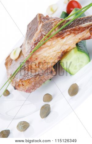 hot red beef meat steak on white plate with capers and tomatoes isolated over white background . shallow dof