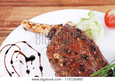 plate on wood : grilled shoulder on plate with chives and tomato served on white plate