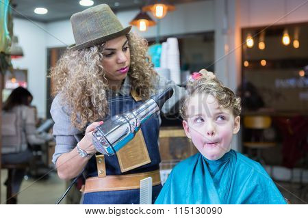 Little Boy Making Faces In Barber Chair