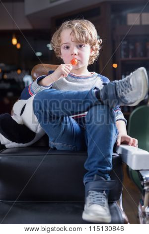 Portrait Of Little Boy Sitting In Chair And Eating Lollipop