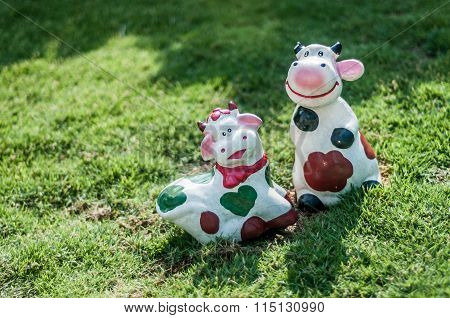 Cows Figurines On The Grass.