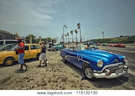 CUBA, HAVANA-JULY 6, 2015: People and classic american cars on a street in Havana.