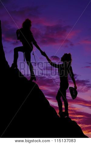 Silhouette Of A Woman Backpacking Reaching Down To Help Other Woman