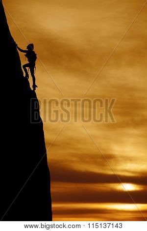 Silhouette Of A Woman Climbing A Large Steep Mountain With A Backpack