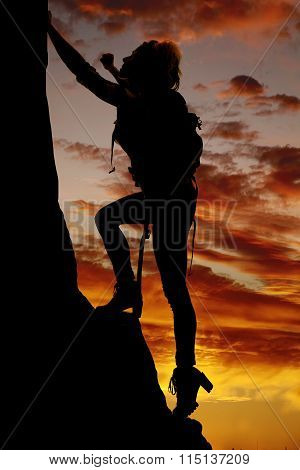 Silhouette Of A Woman Climbing A Steep Mountain In The Sunset