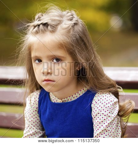 Sad little girl is sitting on the bench, autumn outdoor shoot