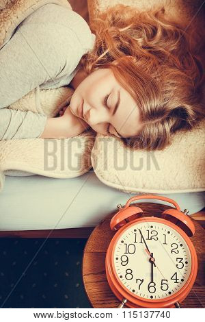 Woman Sleeping In Bed With Set Alarm Clock.