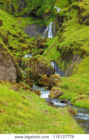 Picturesque cascade step falls. Basalt mountains overgrown with a green grass and moss. July in Iceland