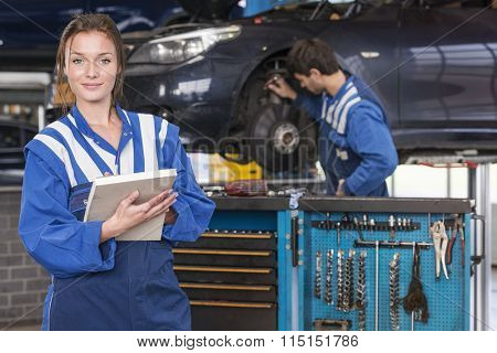 portrait of a female mechanic in a automotive workshop
