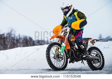 closeup man motorcycle racer on a snow-covered race track