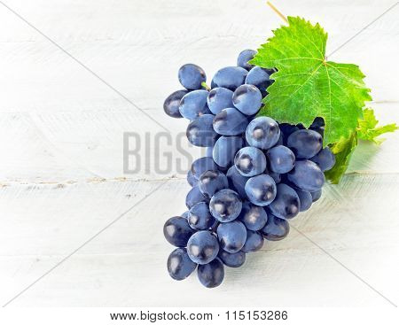 Blue grapes with green leaf on wooden board