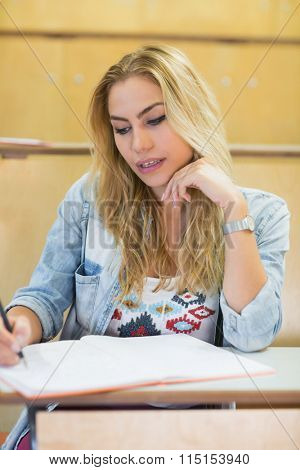 Serious female student writing during class at the lecture hall