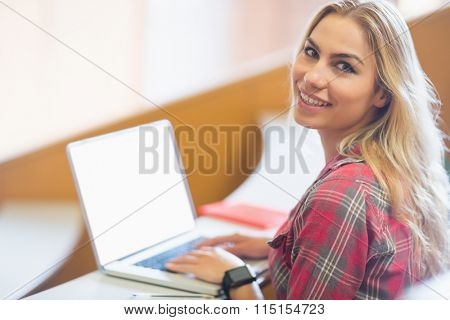 Smiling female student using laptop in lecture hall
