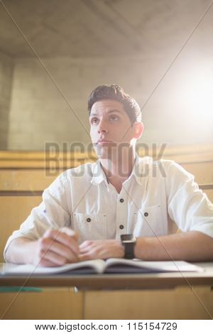Concentrated male student during class in lecture hall