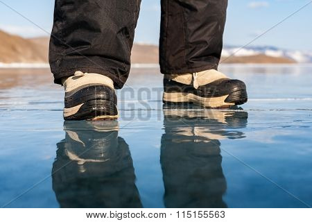 Human foot in shoes on the ice of Lake Baikal