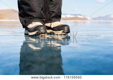 Legs of man on ice. Reflection