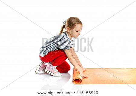 little girl doing gymnastic exercises on yoga mat