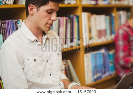 Concentrated male student working on floor in library