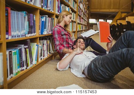 Student reading book while lying on his classmate in library
