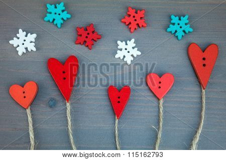 Button love trees under snowflake on grey wooden background.