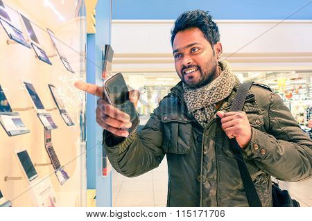 Young Happy Indian Man Pointing Finger To Showcase With Mobile Phones On Display