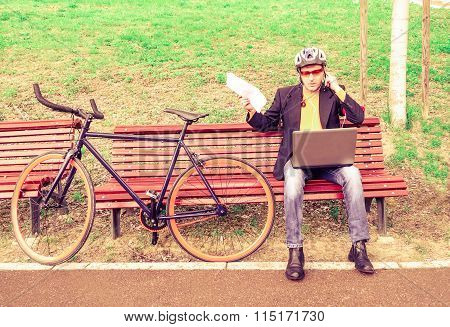 Business Man Working With Laptop And Using Mobile Phone With Earphones Sitting In A Park Bench