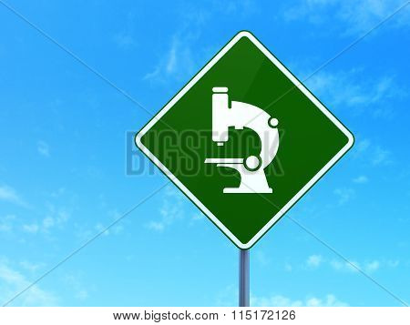 Science concept: Microscope on road sign background