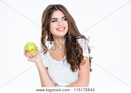 Portrait of a smiling gorgeous woman holding apple and looking away isolated on a white background