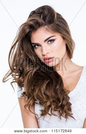 Portrait of a charming woman with long curly hair looking at camera isolated on a white background