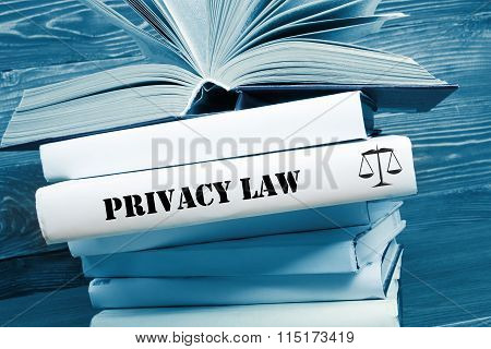 Book with Privacy Law word on table in a courtroom or enforcement office. Toned image