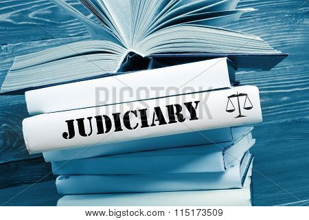 Book with Judiciary word on table in a courtroom or enforcement office. Toned image