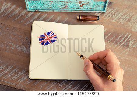 Woman Hand Drawing The Union Jack Flag On Notebook