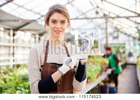 Happy young woman gardener in garden gloves and brown apron standing in greenhouse
