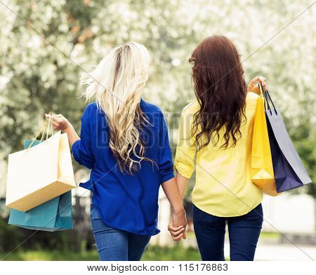 Two fashionable female shoppers holding hands while walking with shopping bags.
