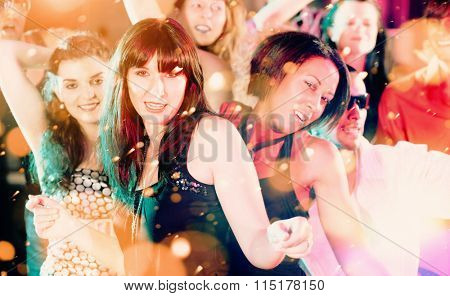 Women and men dancing in club or disco having party, filtered image