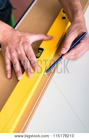 Workman with air level flooring home