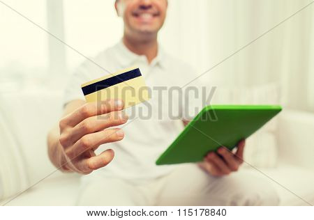 close up of man with credit card and tablet pc