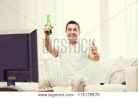 smiling man watching tv and drinking beer at home
