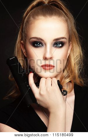 Portrait of young beautiful sexy blonde woman with stylish make-up holding a pistol in her hand