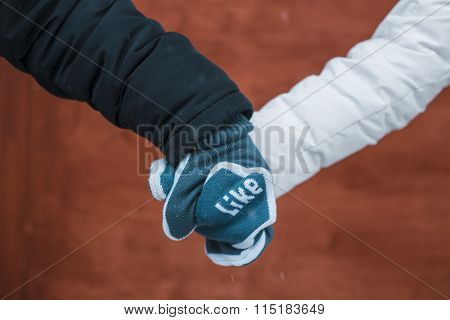 Couple In Love Holding Hands In Mittens