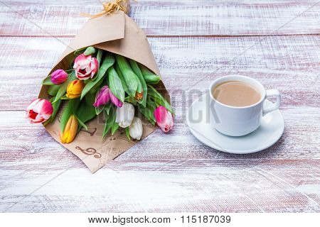 tulips and coffees isolated on a wooden table