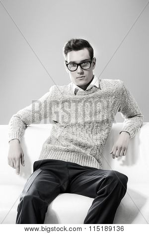 Modern young man sitting relaxed on a sofa. Men's beauty, fashion.