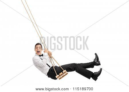 Elegant man with a black bow-tie and suspenders swinging on a wooden swing isolated on white background
