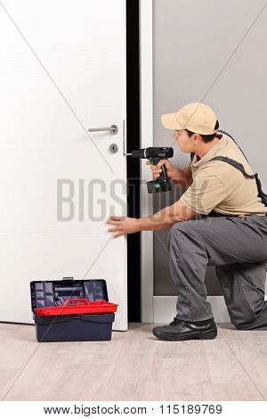 Vertical shot of a young male locksmith installing a door lock with an electric hand drill