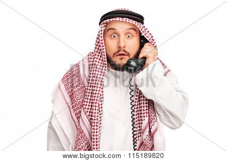 Surprised Arab holding a telephone speaker and looking at the camera isolated on white background