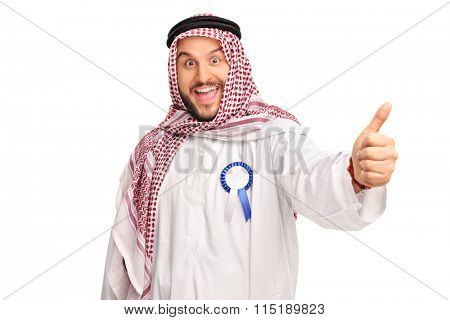 Young cheerful Arab with a blue award ribbon on his robe giving a thumb up isolated on white background
