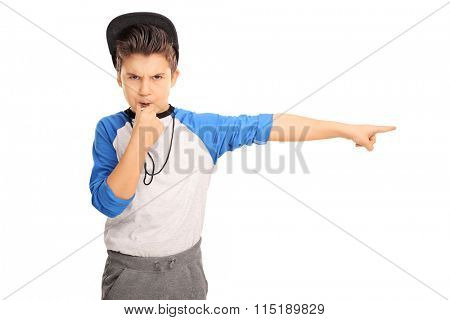 Studio shot of an angry kid in sportswear blowing a whistle and pointing right isolated on white background