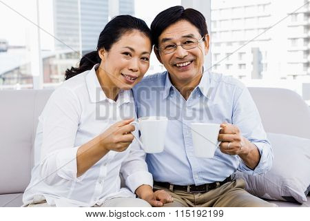 Potrait of couple enjoying coffee on the couch at home