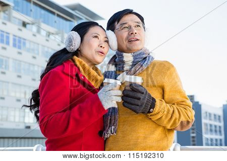 Older asian couple with coffee to go on a cold day